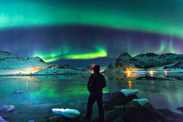 Northern lights at night with lonely man on front Wall mural
