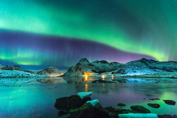 Northern lights at night against the backdrop of beautiful mountains and glaciers