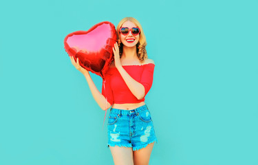 portrait happy smiling woman holding red heart shaped air balloon on colorful blue background