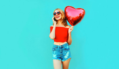 Portrait happy smiling woman calling on smartphone holding red heart shaped air balloon on colorful blue background