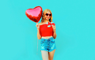 portrait happy smiling young woman holding gift box, red heart shaped air balloon on colorful blue background