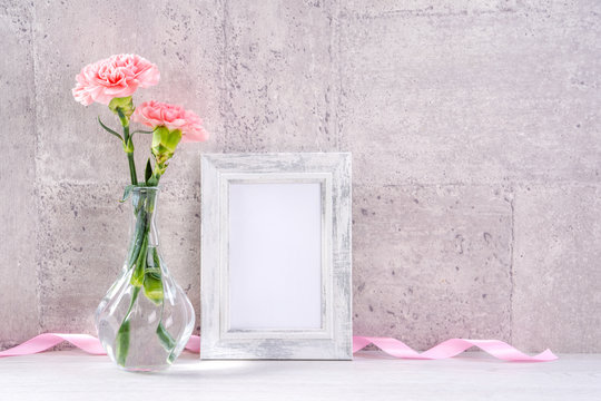Close up, copy space, mock up, beautiful mothers day event concept handmade giftbox decoration photography, blooming fresh carnations with pink color ribbon isolated on gray wallpaper