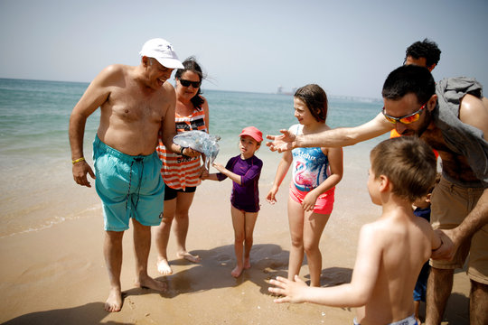Israelis look at a jellyfish at the beach during parliamentary election day, in Zikim beach, southern Israel