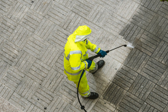 Top view of a Worker cleaning the street sidewalk with high pressure water jet on rainy day
