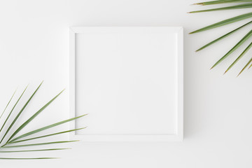 Top view of a white square frame mockup with palm leaf decoration.