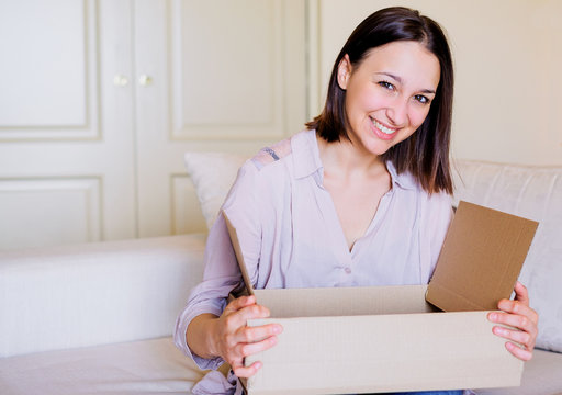 Happy girl opening her online purchase delivery