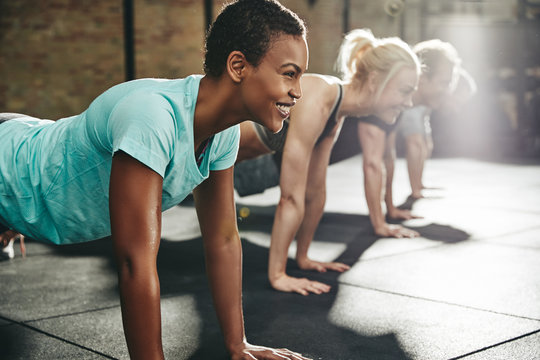 Young woman smiling while doing pushups at the gym