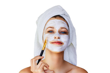 Beautiful young woman applying facial mask on her face with brush. Skin care and treatment, spa, natural beauty and cosmetology concept, isolated over white background