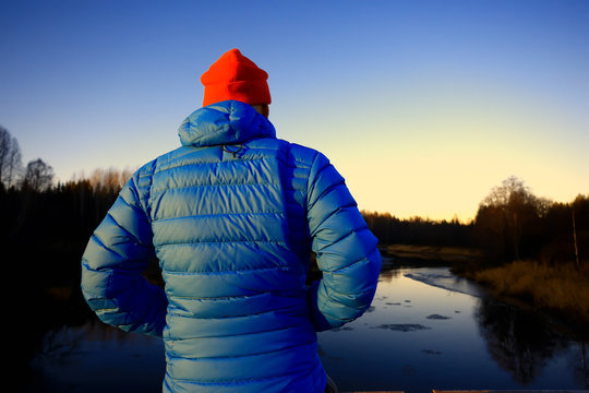 man in sports down jacket landscape winter trekking / down jacket on a tourist, outdoor activities in the north, seasonal landscape