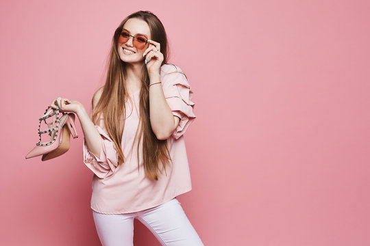 Beautiful and happy blonde model girl with a shiny smile in beige blouse and in fashionable pink sunglasses holding stylish shoes in her hands and posing at the pink background, isolated