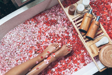 Female legs in bathtub with flower petals and beauty products on wooden tray
