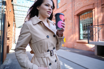 Coffee on the go. Beautiful young woman holding coffee cup and smiling while walking along the street