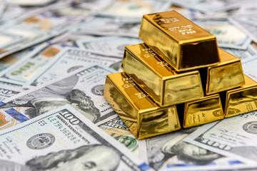 Gold bullion on american dollar banknotes close up