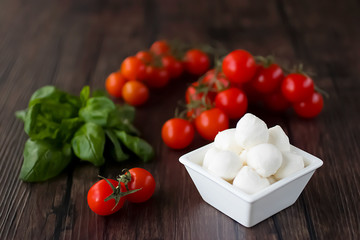 Mozzarella cheese, basil and cherry tomatoes on a brown wooden table. Ingredients for making salad caprese. Mediterranean Kitchen.