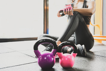 Sport woman sitting and resting after workout or exercise in fitness gym with protein shake or drinking water on floor. Relax concept. Strength training and body build up theme. - Image