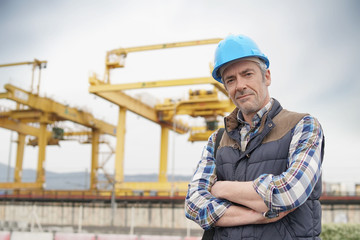 Construction worker on industrial sight looking at camera