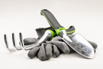 Green gloves with garden tools on a white background
