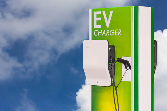 electric vehicle charging (Ev) station and plug of power cable supply for Ev car on blue sky and cloud background