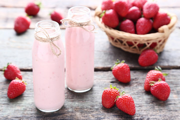 Wall Mural - Smoothie in glass bottles with strawberries on grey wooden table