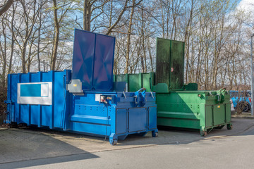 two large garbage compactors standing on a hospital site