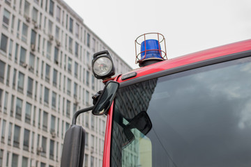 close-up picture of blue lights and sirens on a fire-truck on the background of a multistory building and the sky