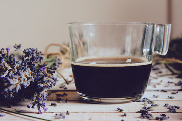 Cup of coffee and fresh lavender flowers, on wooden table.