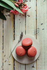 Pink macaroons and cup of coffee, on light wooden table