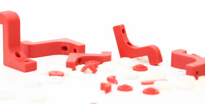 3d printing plastic part red isolated on white background, produced from pla, horizontal view, macro