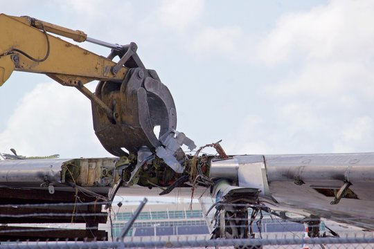 Aircraft wing section being reduced to scrap by a demolition excavator with a claw