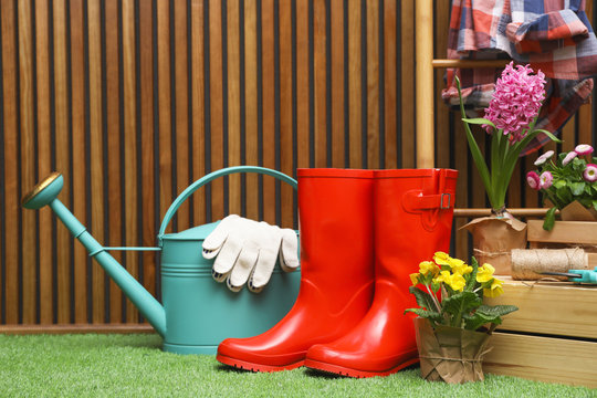 Composition with different gardening tools on artificial grass at wooden wall