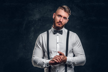 Stylishly dressed young man in shirt with bow tie and suspenders. Studio photo against dark wall background