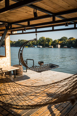 Hammock on wooden terrace next to river