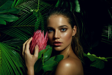 A beautiful tanned girl with natural make-up and wet hair stands in the jungle among exotic plants. Wall mural