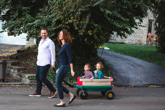 A happy family walks together down the street, children in a wagon