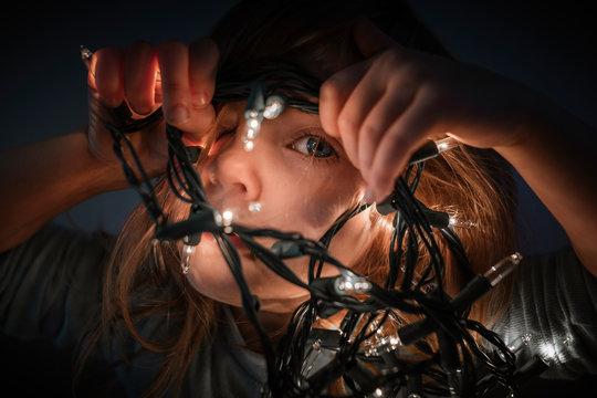 Close up of toddler girl peeking through christmas lights