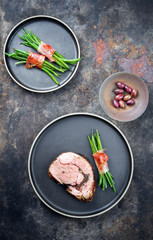 Barbecue marinated Greek lamb roast with kalamata olives and beans rolled in bacon as top view on a modern design plate