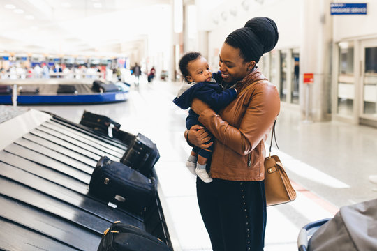 Woman with her son standing near baggage carousel at airport