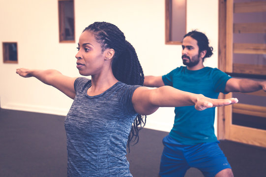 Man and woman practicing yoga indoors