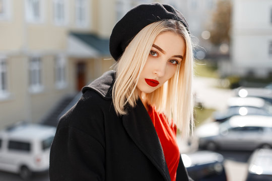 Portrait of a glamorous beautiful blonde woman with red sexy lips in a black coat in an elegant beret in a stylish red shirt on a sunny warm day. Attractive girl fashion model enjoys the sunshine.