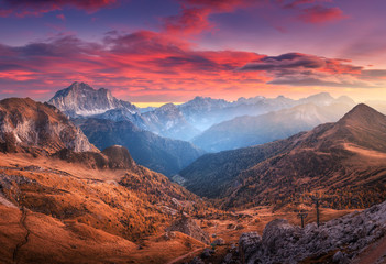 Wall Mural - Colorful red sky with clouds over the beautiful mountains in fog at sunset in autumn. Dolomites, Italy. Landscape with mountain range, hills with orange grass, trees, sky with orange sunlight. Travel