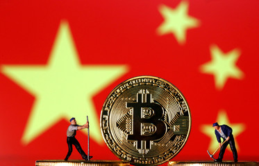Picture illustration of small toy figurines and representations of the Bitcoin virtual currency displayed in front of an image of China's flag