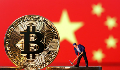 Picture illustration of a small toy figurine and representations of the Bitcoin virtual currency displayed in front of an image of China's flag