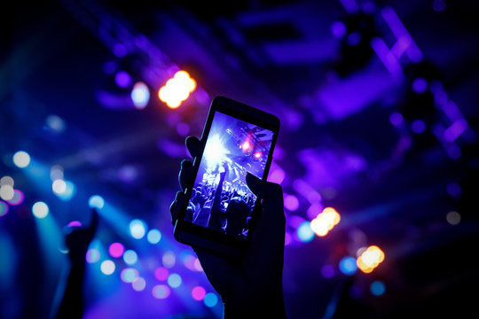 Filming a concert on mobile phone camera, stage blue light