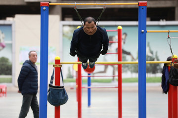Sun Rongchun, 57, exercises with an improvised cervical traction device attached to a high bar at a sports complex in Shenyang