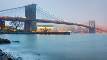 Fototapete - Brooklyn bridge at foggy rainy evening, New York City