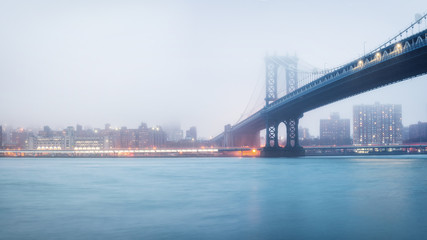 Fotomurales - Manhattan bridge and Manhattan at foggy evening, New York City