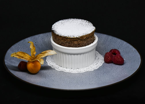 A chocolate soufflé sits on a grey plate with simple fruit garnishes