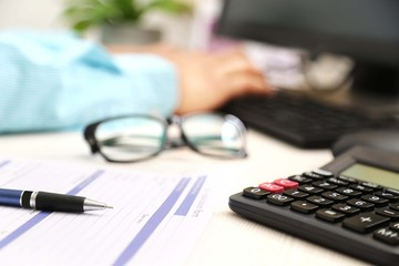 Picture of man hand is typing on keyboard. Picture of application form, pen, calculator and glasses.