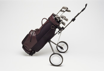Golf clubs in bag on trolley, white background