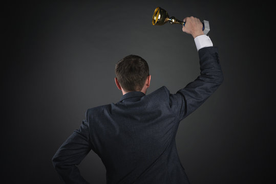 Businessman with a golden cup award trophy in hand raised up. First place concept background. Best worker award. Business achievement.